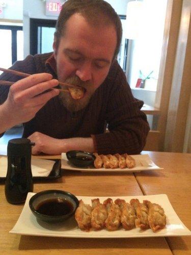 Photo of Okla Elliott biting into fried dumpling, by Renata Fuchs